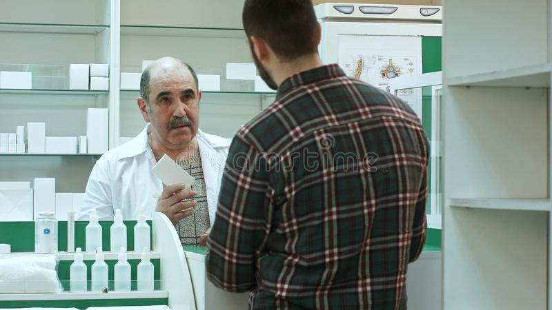 Cliente masculino novo que obtém a bolha dos comprimidos do farmacêutico na drograria imagem de stock