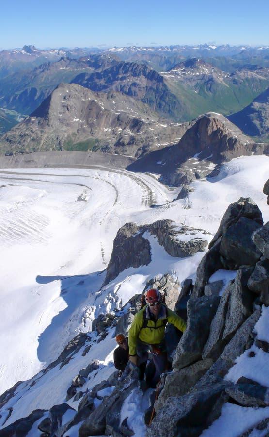 Cliente masculino principal do guia da montanha à cimeira de um pico alpino alto em um dia de verão bonito fotos de stock