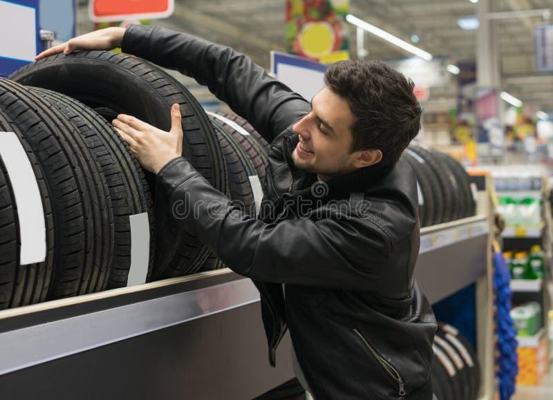 Cliente masculino que elige los nuevos neumáticos fotos de archivo