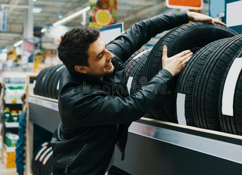 Cliente masculino que escolhe pneus novos no supermercado imagens de stock