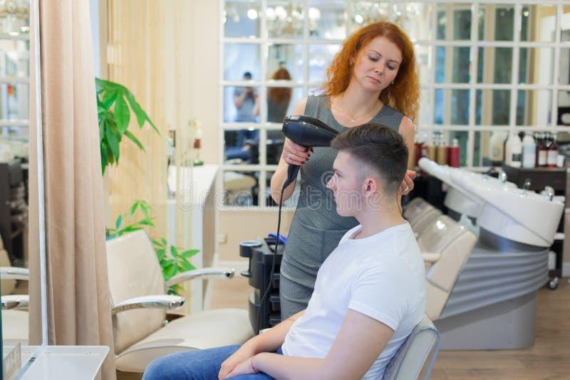 Cliente masculino que obtém o corte de cabelo O cabeleireiro da menina seca meu cabelo um indivíduo novo, atrativo em um salão de fotos de stock