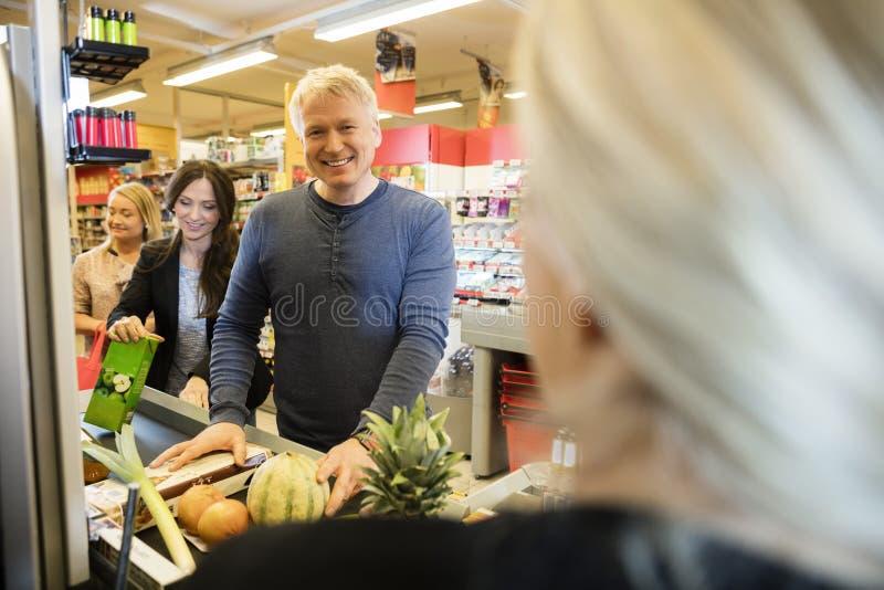 Cliente masculino que se coloca en el contador de pago y envío en supermercado imagen de archivo libre de regalías