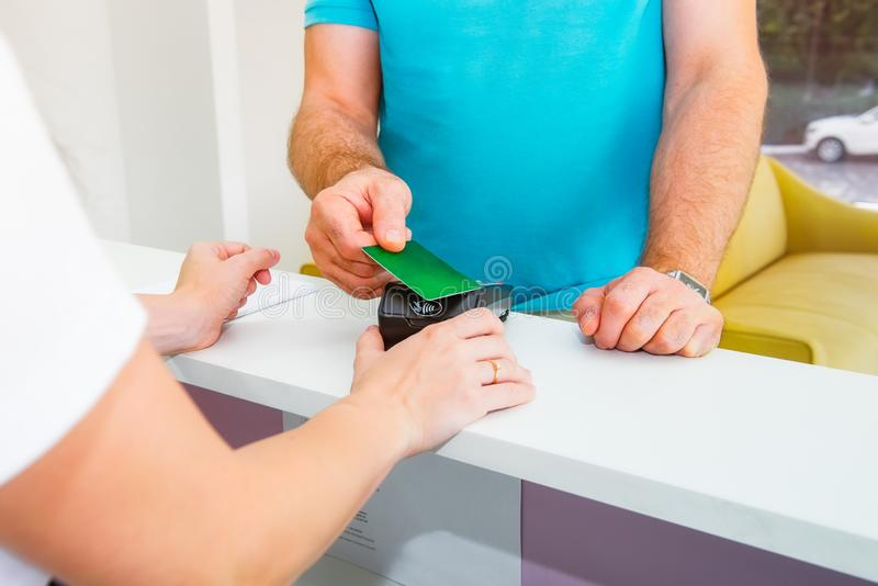 Cliente na mesa de recepção que faz o pagamento sem contato com o cartão de crédito da tecnologia do nfc na loja, clínica, serviç imagem de stock