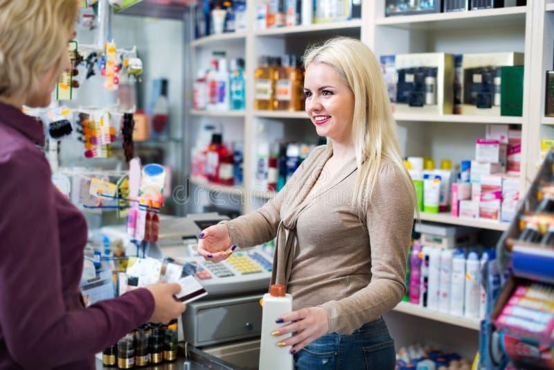 Cliente positivo en la tienda que paga en la caja registradora imagenes de archivo