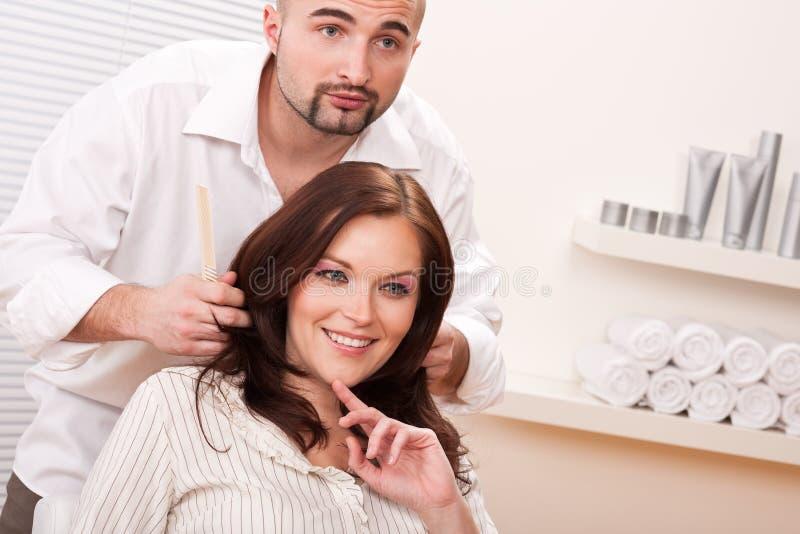 Cliente profesional del peine del peluquero en el salón imagen de archivo