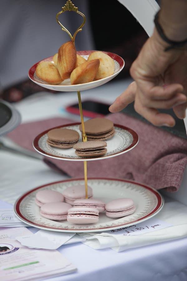 Cliente que aponta aos bolinhos de amêndoa e aos outros doces em um suporte a três níveis do bolo imagem de stock