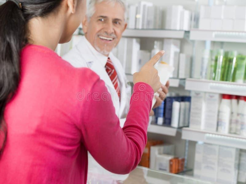 Cliente que aponta em produtos quando químico Looking At Her fotos de stock