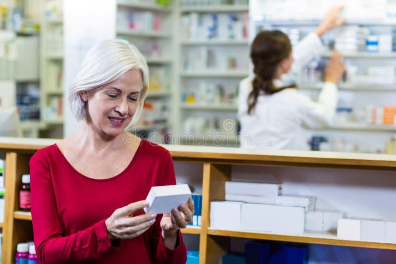 Cliente que comprueba una caja de la píldora imagen de archivo