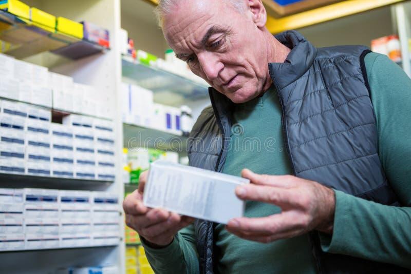 Cliente que comprueba una caja de la píldora foto de archivo