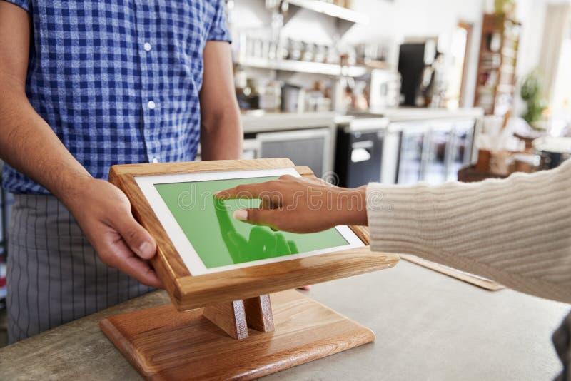 Cliente que consume las ventas terminales en el café, cierre de la pantalla táctil foto de archivo