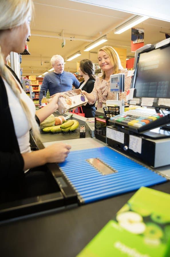 Cliente que da el paquete al cajero femenino At Checkout Counter foto de archivo
