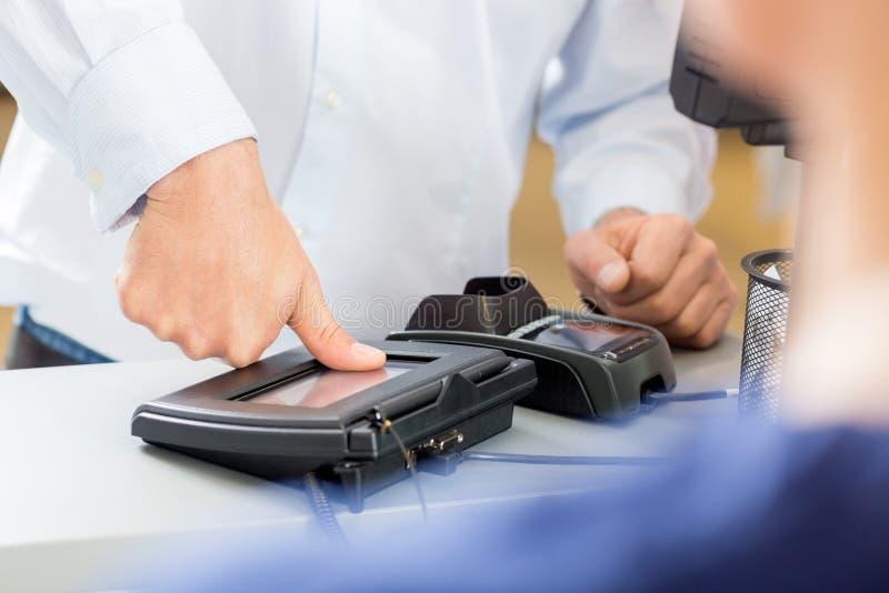 Cliente que da la impresión del pulgar para hacer el pago fotos de archivo
