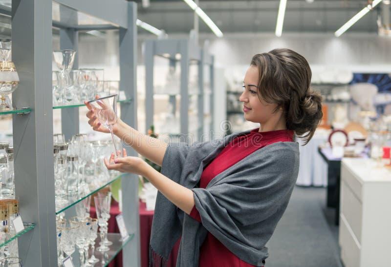 Cliente que elige platos del utensilio de los cristales en la alameda del supermercado fotografía de archivo
