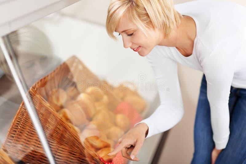 Cliente que escolhe o pão do armário de exposição no café fotos de stock