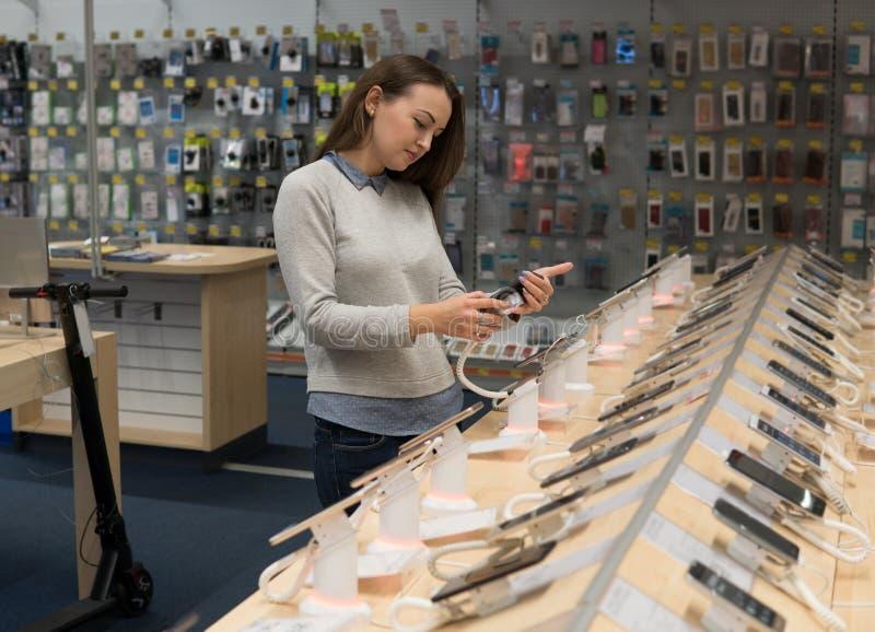 Cliente que escolhe o smartphone na loja do telefone celular foto de stock