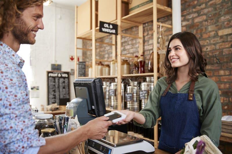 Cliente que faz o pagamento sem contato para a compra na verificação geral da mercearia foto de stock royalty free