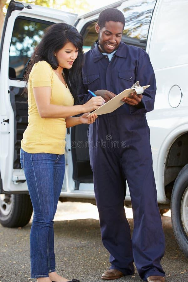 Cliente que firma para la entrega del mensajero fotos de archivo
