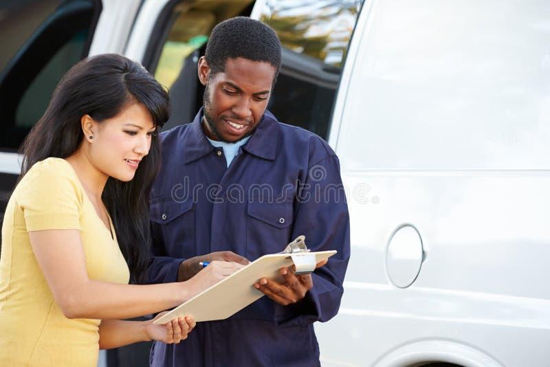 Cliente que firma para la entrega del mensajero fotografía de archivo libre de regalías