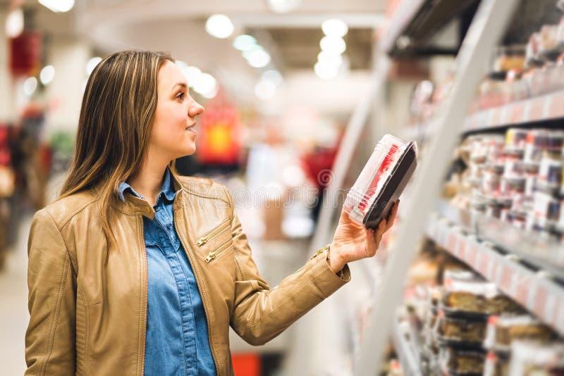 Cliente que guarda o pacote do alimento na mercearia imagem de stock royalty free