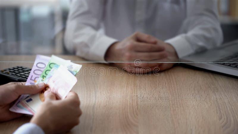 Cliente que hace el depósito euro en el banco, crecimiento del negocio, ahorros, gasto personal imágenes de archivo libres de regalías