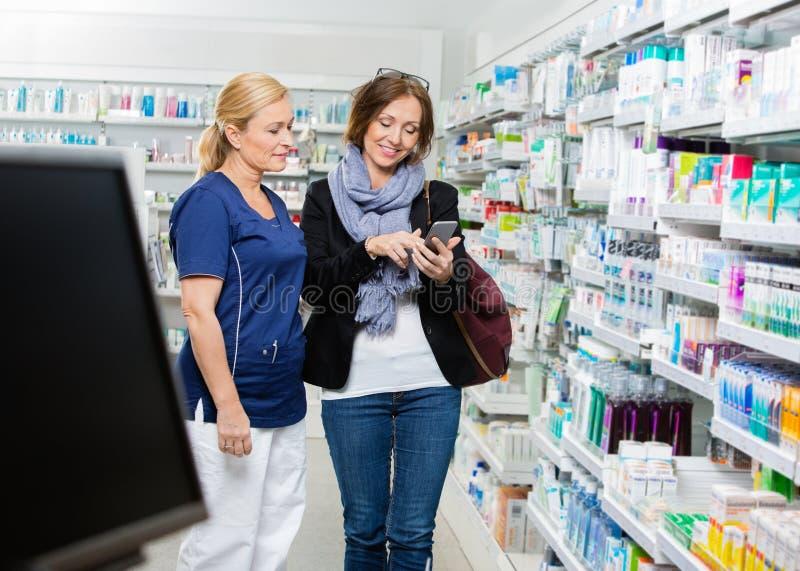 Cliente que mostra o telefone esperto ao químico In imagem de stock royalty free