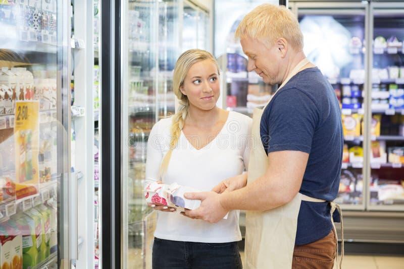Cliente que olha o supermercado de Assisting Her In do vendedor fotografia de stock