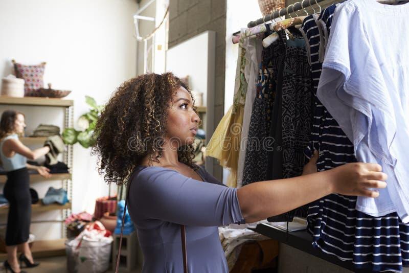 Cliente que olha a roupa em um trilho de suspensão em um boutique imagens de stock royalty free