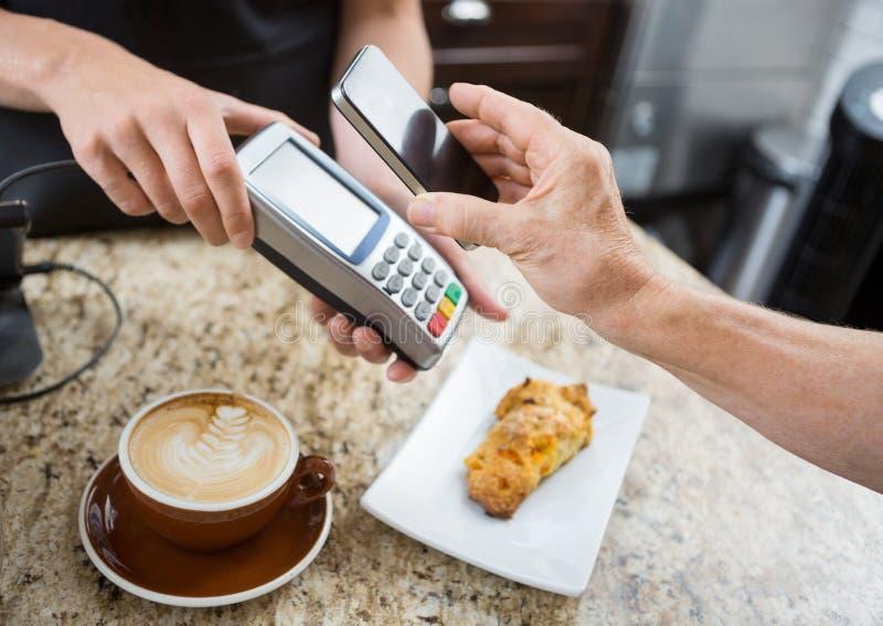 Cliente que paga através do telefone celular sobre fotografia de stock