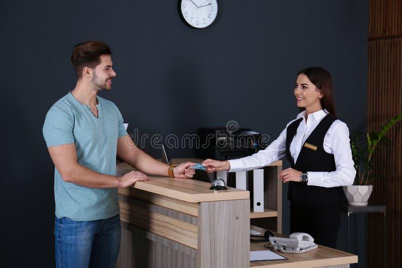Cliente que paga con la tarjeta de crédito servicio al recepcionista en el escritorio foto de archivo libre de regalías