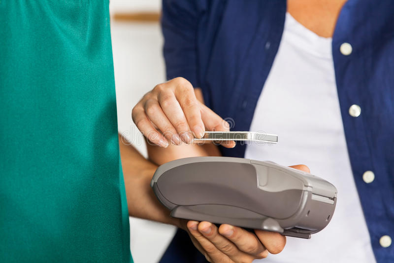 Cliente que paga con Smartphone usando NFC imágenes de archivo libres de regalías