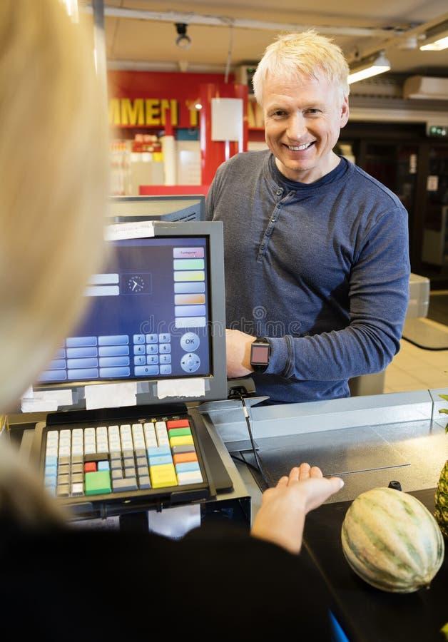 Cliente que paga con Smartwatch mientras que cajero Guiding Him imagenes de archivo