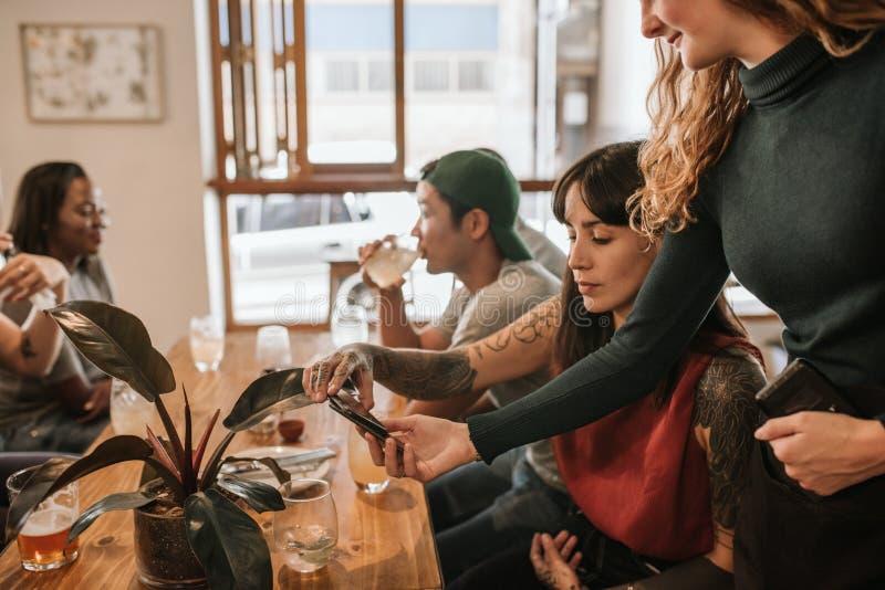 Cliente que paga a conta com seu smartphone em um restaurante imagem de stock