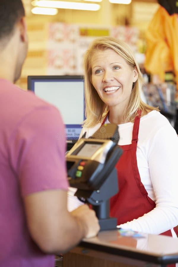 Cliente que paga hacer compras en el pago y envío del supermercado fotos de archivo