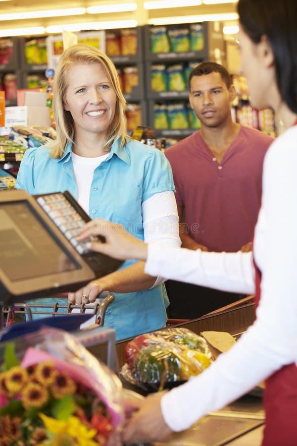 Cliente que paga hacer compras en el pago y envío del supermercado fotografía de archivo libre de regalías