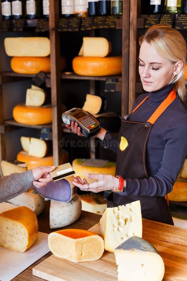Cliente que paga la pedido del queso en tienda de ultramarinos fotos de archivo