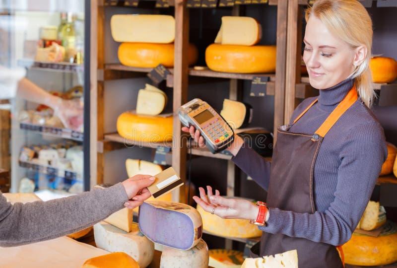 Cliente que paga la pedido del queso en tienda de ultramarinos fotografía de archivo libre de regalías