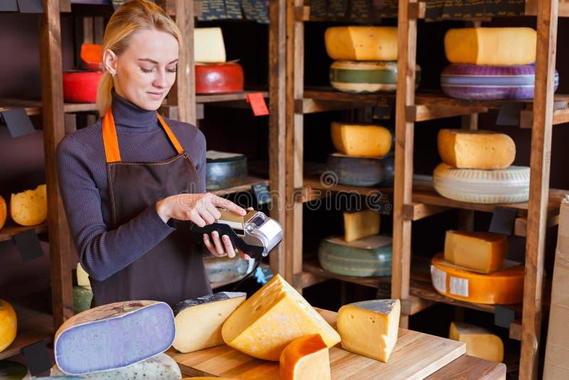 Cliente que paga la pedido del queso en tienda de ultramarinos fotos de archivo libres de regalías