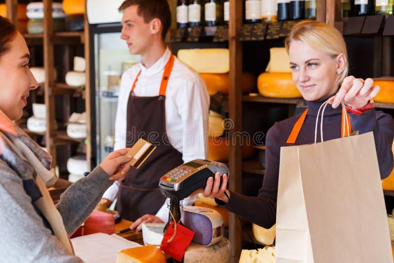 Cliente que paga la pedido del queso en tienda de ultramarinos imagen de archivo