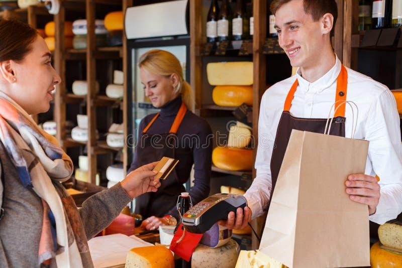 Cliente que paga la pedido del queso en tienda de ultramarinos fotografía de archivo