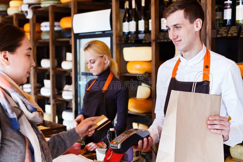 Cliente que paga la pedido del queso en tienda de ultramarinos foto de archivo libre de regalías