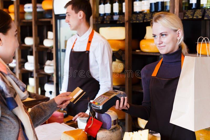 Cliente que paga la pedido del queso en tienda de ultramarinos imagenes de archivo