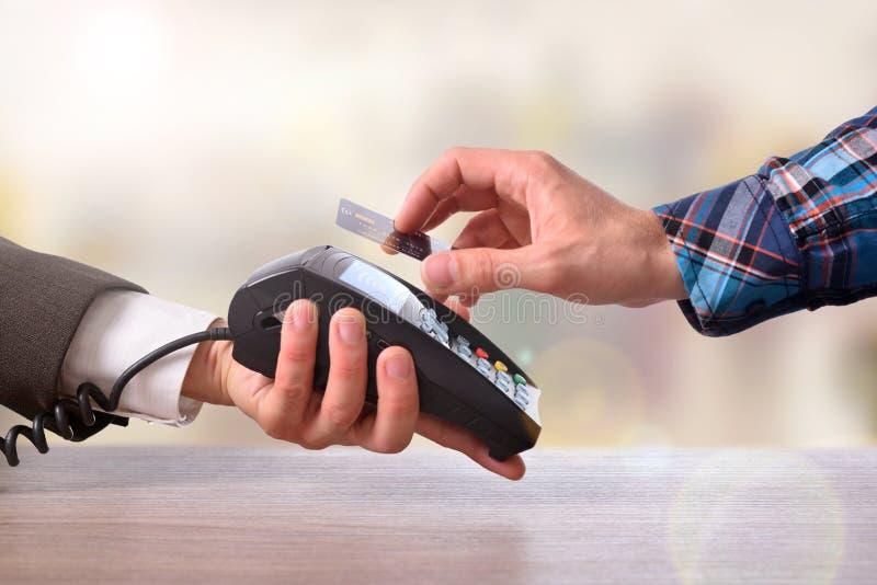 Cliente que paga um comerciante com opinião dianteira do cartão sem contato imagens de stock