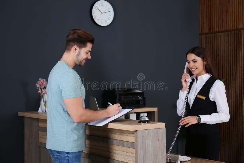 Cliente que se registra en el escritorio mientras que recepcionista que habla en el teléfono foto de archivo