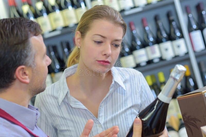 Cliente que toma o conselho sobre o vinho fotografia de stock