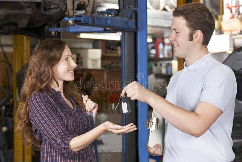 Cliente satisfecho que recoge el coche de mecánico del garaje imagen de archivo