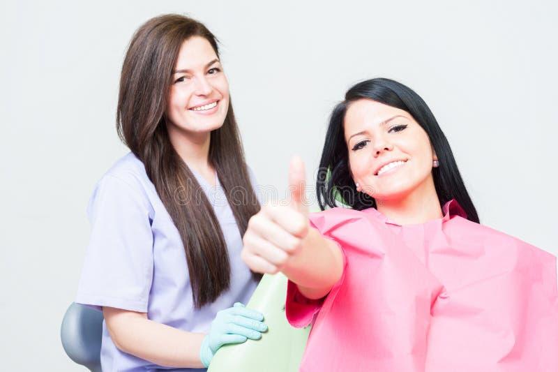Cliente satisfeito da mulher no dentista que mostra como foto de stock