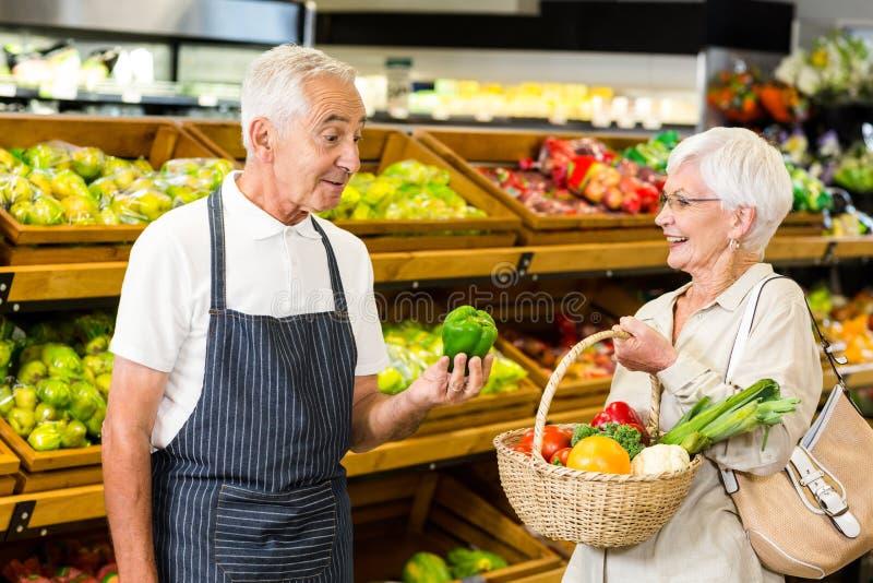 Cliente senior e lavoratore che discutono le verdure immagini stock libere da diritti