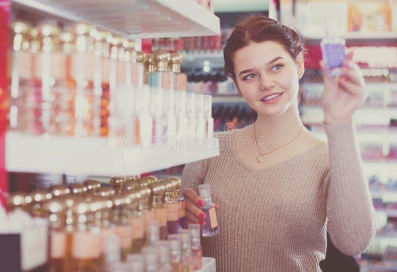 Cliente sonriente de la mujer que decide sobre variantes del perfume en cosméticos fotografía de archivo libre de regalías