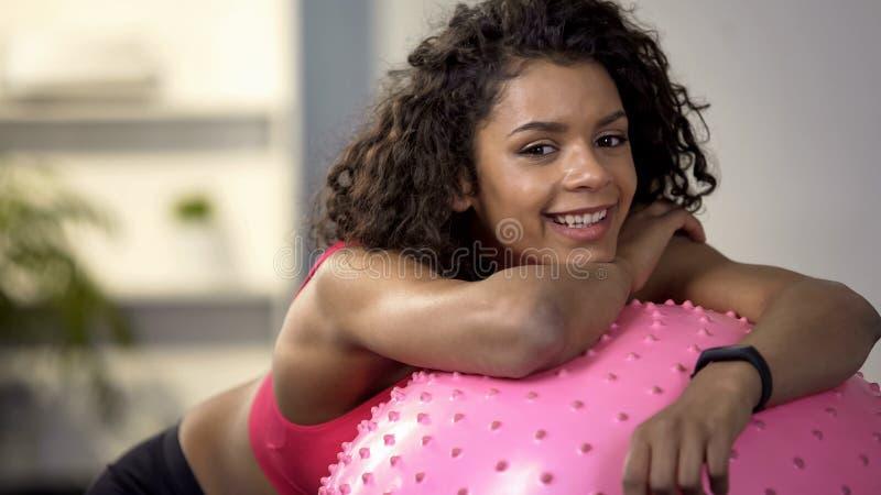 Cliente sonriente del club de deporte que se inclina en la bola de la aptitud, servicio del gimnasio, rotura del entrenamiento foto de archivo