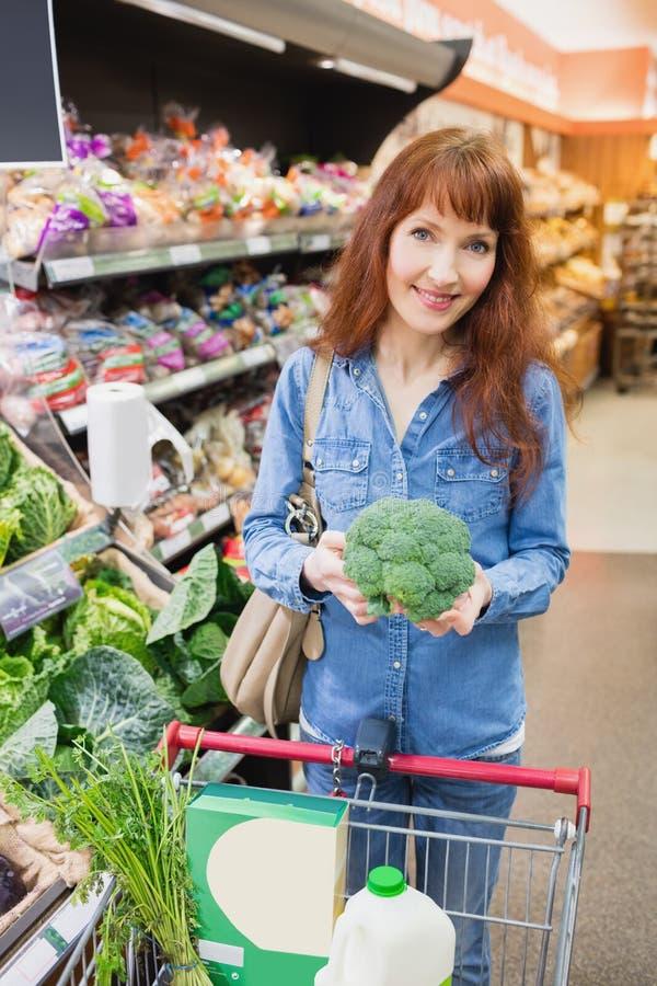 Cliente sonriente que sostiene un bróculi imagenes de archivo